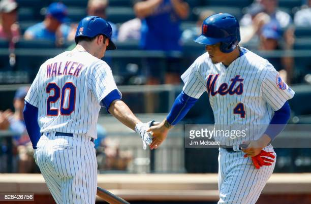 Wilmer Flores of the New York Mets celebrates his fifth inning home run against the Texas Rangers with teammate Neil Walker at Citi Field on August 9...