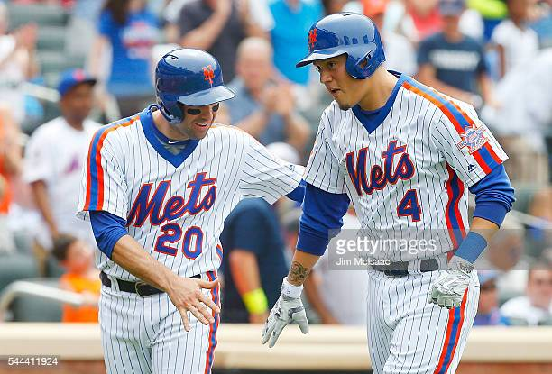 Wilmer Flores of the New York Mets celebrates his fifth inning two run home run against the Chicago Cubs with teammate Neil Walker at Citi Field on...