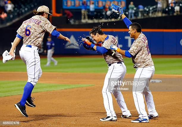 Wilmer Flores of the New York Mets celebrates his ninth inning game winning sacrifice fly against the Colorado Rockies with teammates Juan Lagares...