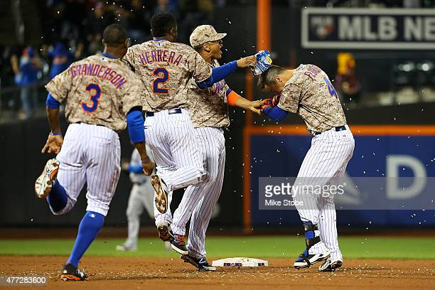 Wilmer Flores of the New York Mets celebrates with his teamates after hitting the game winning single in the eleventh inning against the Toronto Blue...