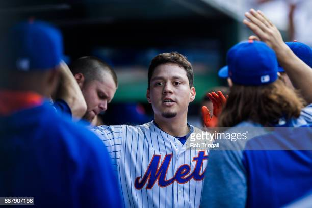 Wilmer Flores of the New York Mets gets greeted by his teammates after scoring a run during the game against the Milwaukee Brewers at Citi Field on...