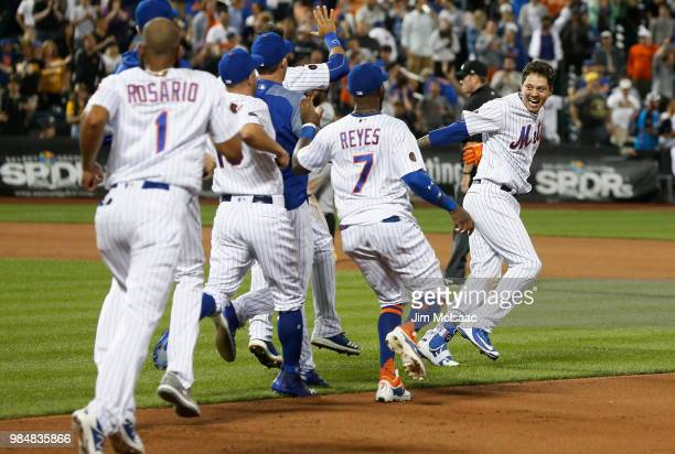 Wilmer Flores of the New York Mets is chased down by his teammates in celebration of his tenth inning game winning base hit against the Pittsburgh...