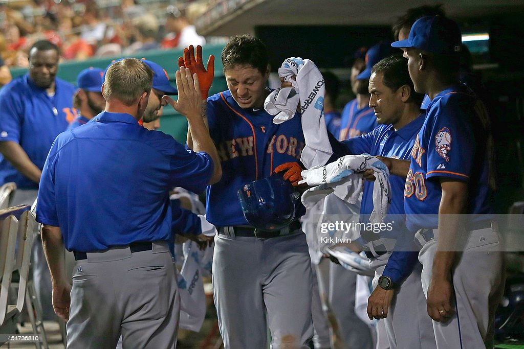 Wilmer Flores #4 of the New York Mets is congratulated by his teammates after hitting a home run during the fifth inning against the Cincinnati Reds at Great American Ball Park on September 5, 2014 in Cincinnati, Ohio. New York defeated Cincinnati 14-5.