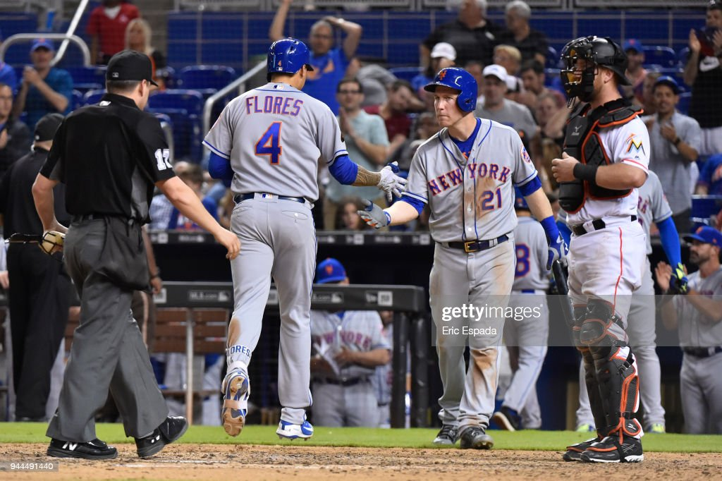Wilmer Flores #4 of the New York Mets is congratulated by Todd Frazier #21 after hitting a home run in the eighth inning against the Miami Marlins at Marlins Park on April 10, 2018 in Miami, Florida.