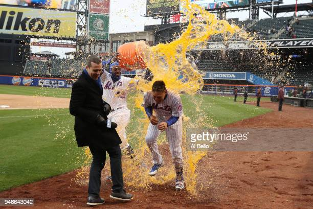 Wilmer Flores of the New York Mets is hit with a gatorade bath by teamate Yoenis Cespedes after he hit a walkoff home run in the ninth inning to win...