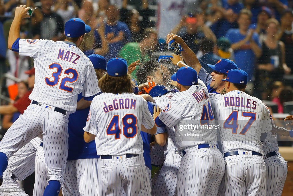 Wilmer Flores #4 of the New York Mets is mobbed by his teammates at home plate after his ninth inning game winning home run against the Oakland Athletics at Citi Field on July 22, 2017 in the Flushing neighborhood of the Queens borough of New York City.
