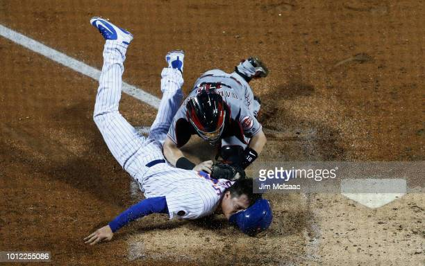 Wilmer Flores of the New York Mets is tagged out at home plate in the third inning by Tucker Barnhart of the Cincinnati Reds at Citi Field on August...