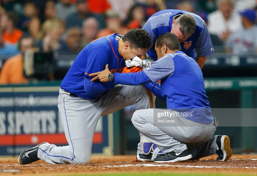 Wilmer Flores #4 of the New York Mets is tended to by training staff after fouling a ball off his face in the fourth inning against the Houston Astros in game two of a double-header at Minute Maid Park on September 2, 2017 in Houston, Texas.