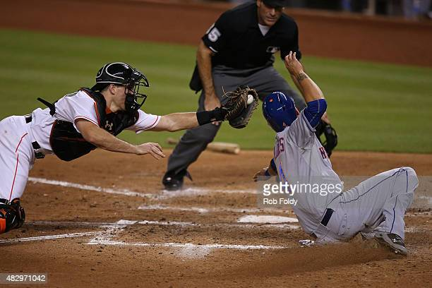 Wilmer Flores of the New York Mets slides safely into home plate past JT Realmuto of the Miami Marlins to score a run during the sixth inning of the...