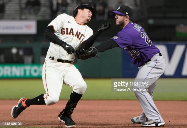 Wilmer Flores of the San Francisco Giants gets caught in a rundown and tagged out by C.J. Cron of the Colorado Rockies in the seventh inning at...