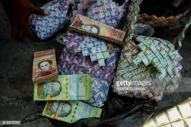 Wilmer Rojas shows the purses he sewn up, using Bolivar bills in Caracas, on January 30, 2018. - A young Venezuelan tries to make a living out of...