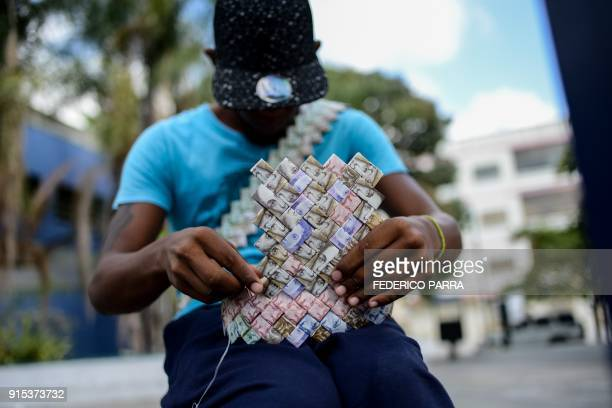 TOPSHOT Wilmer Rojas sists at a bus stop in Caracas as he sews Bolivar bills to make a paper crown on January 30 2018 A young Venezuelan tries to...