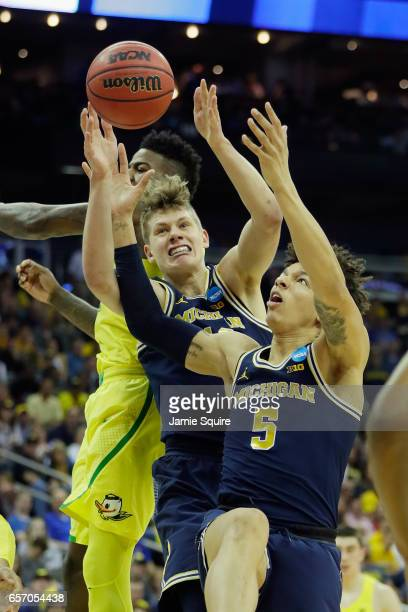 J Wilson and Moritz Wagner of the Michigan Wolverines battle for a rebound in the second half against the Oregon Ducks during the 2017 NCAA Men's...