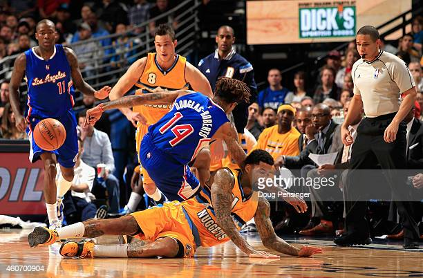 Wilson Chandler of the Denver Nuggets and Chris DouglasRoberts of the Los Angeles Clippers collide as they pursue a loose ball as Danilo Gallinari of...