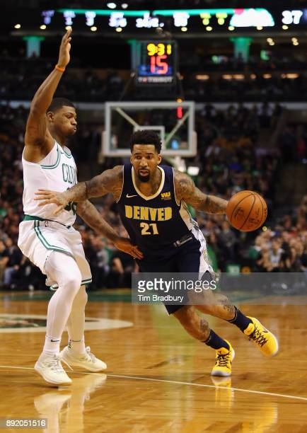 Wilson Chandler of the Denver Nuggets dribbles against Marcus Smart of the Boston Celtics during the first half at TD Garden on December 13 2017 in...