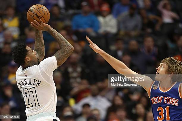 Wilson Chandler of the Denver Nuggets puts up a shot over Ron Baker of the New York Knicks at the Pepsi Center on December 17 2016 in Denver Colorado...