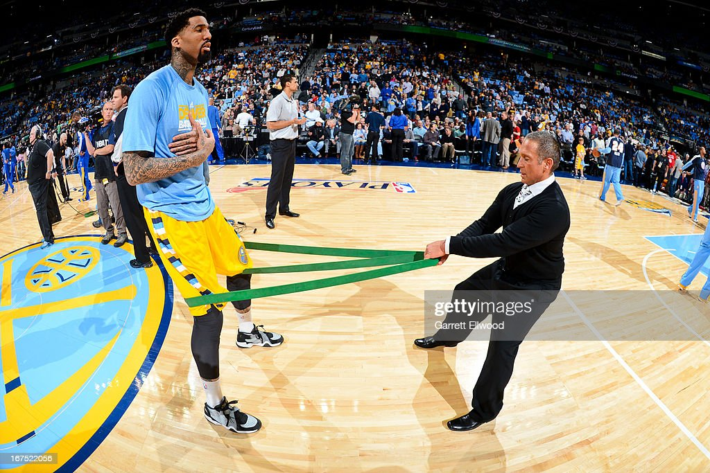 Wilson Chandler #21 of the Denver Nuggets stretches with a trainer before playing against the Golden State Warriors in Game Two of the Western Conference Quarterfinals during the 2013 NBA Playoffs on April 23, 2013 at the Pepsi Center in Denver, Colorado.