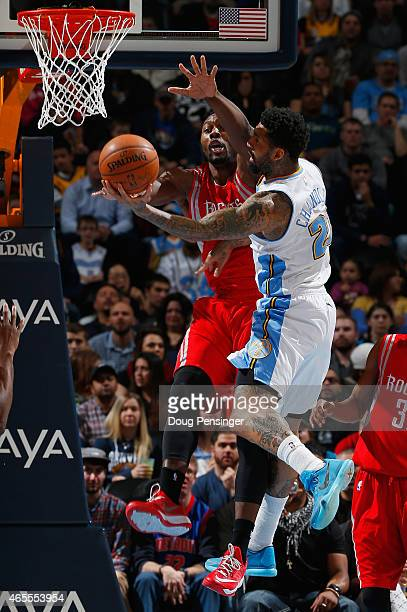 Wilson Chandler of the Denver Nuggets tries to get off a shot against Joey Dorsey of the Houston Rockets at Pepsi Center on March 7 2015 in Denver...