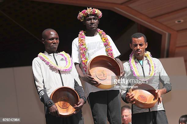 Wilson Chebet of Kenya, Lawrence Cherono of Kenya, and Deribe Robi of Ethiopia pose for a photograph in the winners' ceremony after the Honolulu...