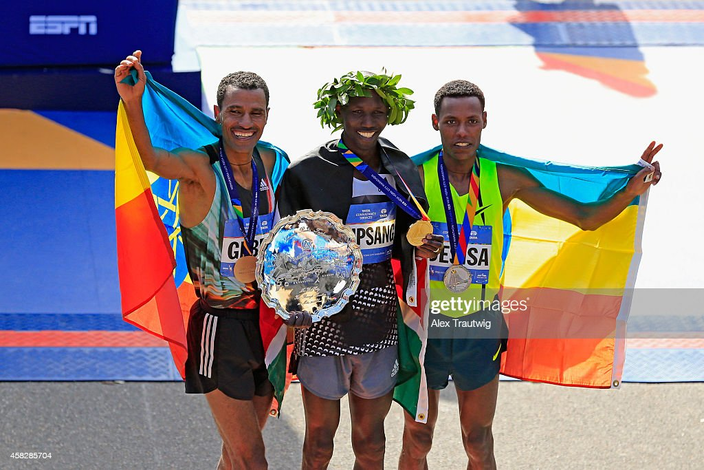 Wilson Kipsang (C) of Kenya celebrates with the first place trophy alongside second place Lelisa Desisa Benti (R) of Ethiopia and third place Gebre Gebremariam (L) of Ethiopia after the Pro Men's division during the 2014 TCS New York City Marathon in Central Park on November 2, 2014 in New York City.