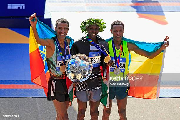 Wilson Kipsang of Kenya celebrates with the first place trophy alongside second place Lelisa Desisa Benti of Ethiopia and third place Gebre...