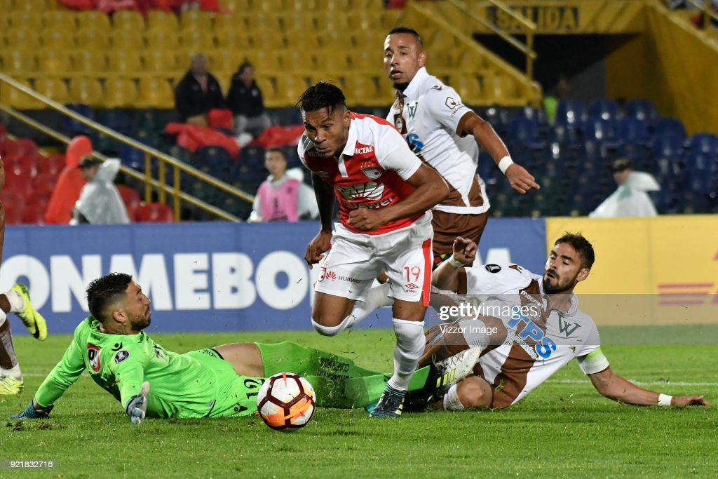 Wilson Morelo of Independiente Santa Fe fights for the ball with goalkeeper Mauricio Viana (L) and Ezequiel Luna (R) of Santiago Wanderers during a second leg match between Independiente Santa Fe and Santiago Wanderers as part of phase 3 of Copa Conmebol Libertadores 2018 at Nemesio Camacho Stadium on February 20, 2018 in Bogota, Colombia.