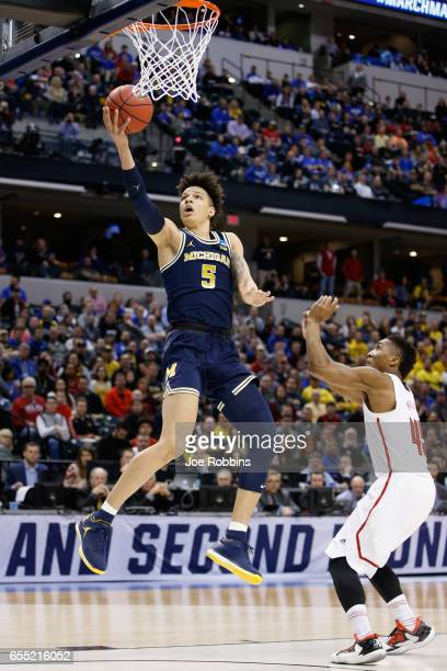 J Wilson of the Michigan Wolverines lays it up for a shot against Donovan Mitchell of the Louisville Cardinals in the first half during the second...
