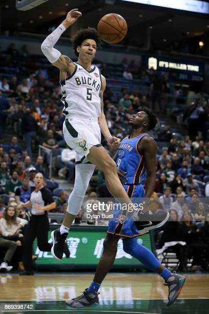 J Wilson of the Milwaukee Bucks dunks the ball past Jerami Grant of the Oklahoma City Thunder in the fourth quarter at the Bradley Center on October...