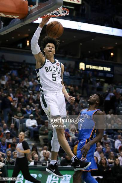 J Wilson of the Milwaukee Bucks dunks the ball past Jerami Grant of the Oklahoma City Thunder in the fourth quarter at the Bradley Center on October...
