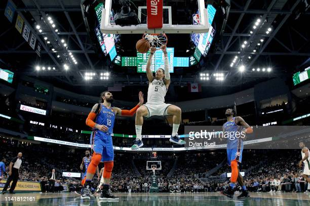 J Wilson of the Milwaukee Bucks dunks the ball past Steven Adams of the Oklahoma City Thunder in the third quarter at the Fiserv Forum on April 10...