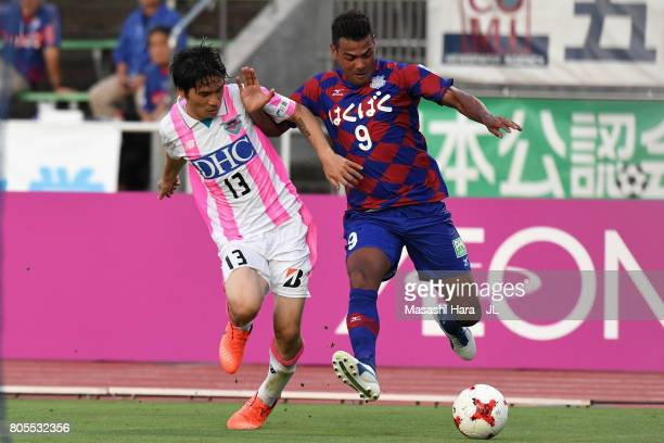 Wilson of Ventforet Kofu and Yuzo Kobayashi of Sagan Tosu compete for the ball during the JLeague J1 match between Ventforet Kofu and Sagan Tosu at...
