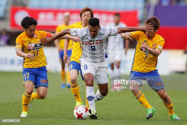 Wilson of Ventforet Kofu controls the ball under pressure of Shingo Tomita and Hiroaki Okuno of Vegalta Sendai during the J.League J1 match between...