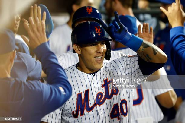 Wilson Ramos of the New York Mets celebrates with teammates in the dugout after hitting a two run home run against the San Francisco Giants during...