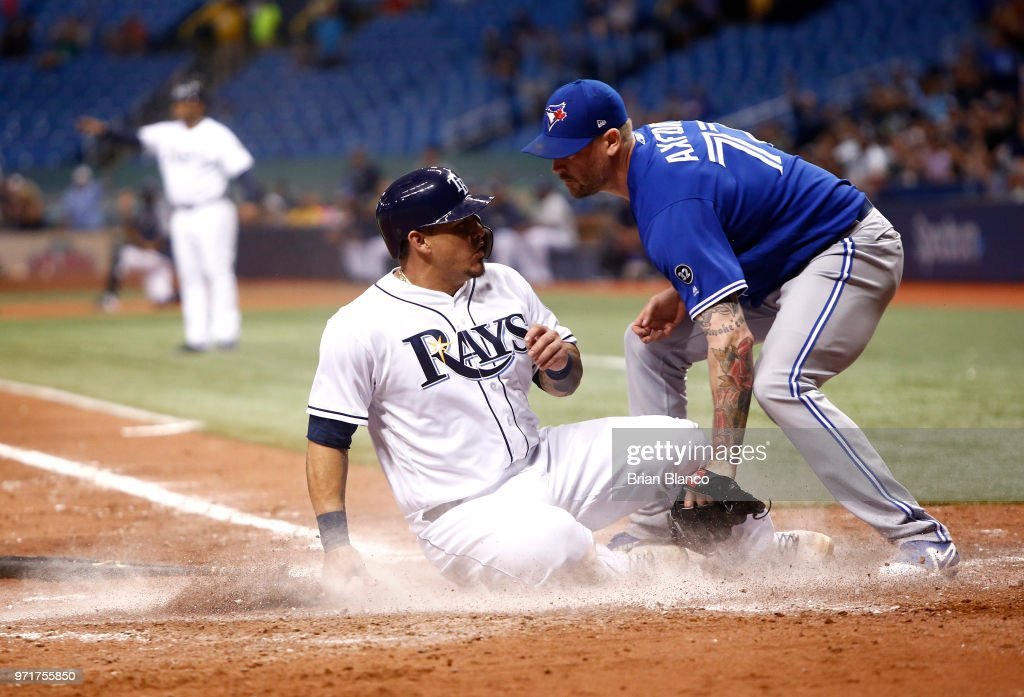 Wilson Ramos #40 of the Tampa Bay Rays slides home safely ahead of pitcher John Axford #77 of the Toronto Blue Jays to score off of a throwing error by Axford during the seventh inning of a game on June 11, 2018 at Tropicana Field in St. Petersburg, Florida.