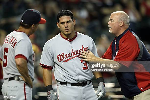 Wilson Ramos of the Washington Nationals is looked at by manager Jim Riggleman and a trainer after being hit by a foul ball during the Major League...