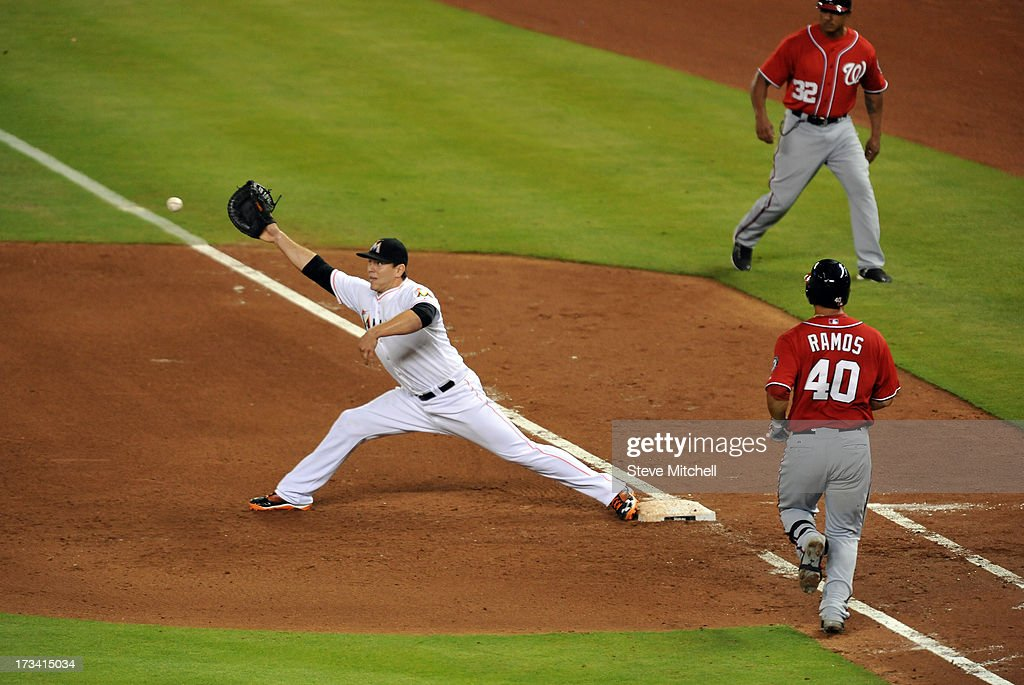 Wilson Ramos #40 of the Washington Nationals reaches first base as Logan Morrison #5 of the Miami Marlins reaches for an errant throw by Ed Lucas (not pictured) during the fifth inning at Marlins Park on July 13, 2013 in Miami, Florida.