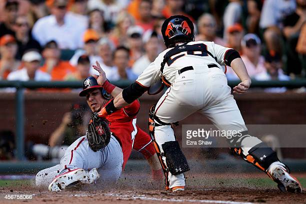 Wilson Ramos of the Washington Nationals scores on a single by Asdrubal Cabrera as Buster Posey of the San Francisco Giants tries to make the tag in...