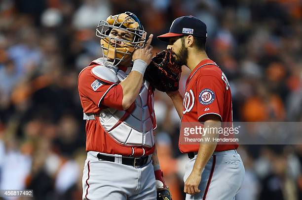 Wilson Ramos talks to Gio Gonzalez of the Washington Nationals after Gonzalez commited an error in the second inning against the San Francisco Giants...