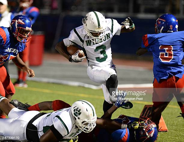Wilson RB Larry Frazier leaps over Anacostia defenders during second quarter action on September 13 2013 in Washington DC