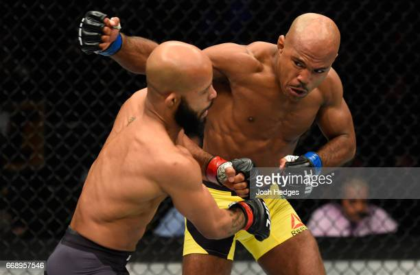 Wilson Reis of Brazil punches Demetrious Johnson in their UFC flyweight fight during the UFC Fight Night event at Sprint Center on April 15 2017 in...
