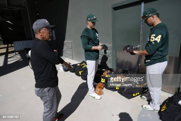 Wilson rep helps Dustin Garneau and Santiago Chavez of the Oakland Athletics check out Wilson catcher gloves prior to leaving for a game against the...