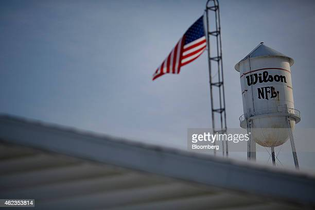 Wilson Sporting Goods Co signage is seen on a water tower as a US flag flies outside of the company's factory in Ada Ohio US on Monday Jan 26 2015...