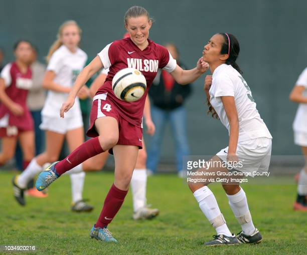 Wilson's Sierra Hancock left tries to maneuver around Poly's Daria Manzano in Long Beach CA on Tuesday January 21 2014 Poly defeated Wilson 10 in...