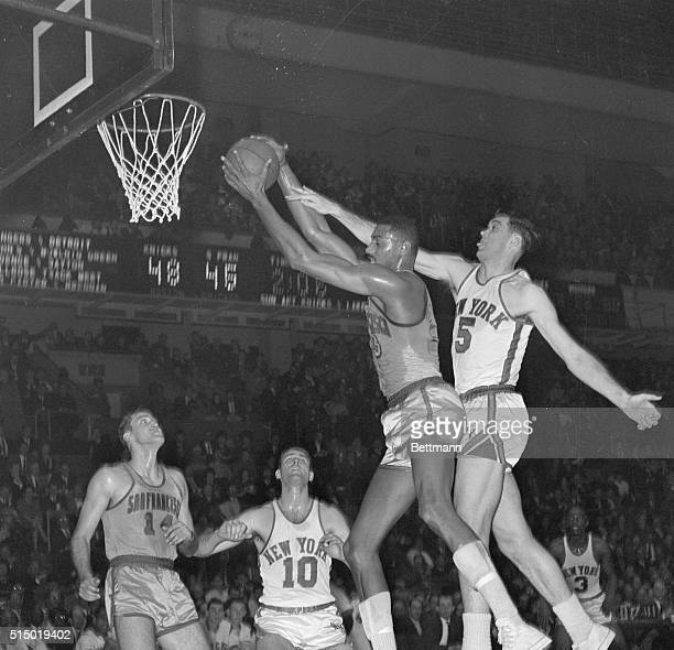 Wilt Chamberlain, center for the San Francisco Warriors, steals away a rebound from New York Knicks' center Gene Conley during a game at Madison...