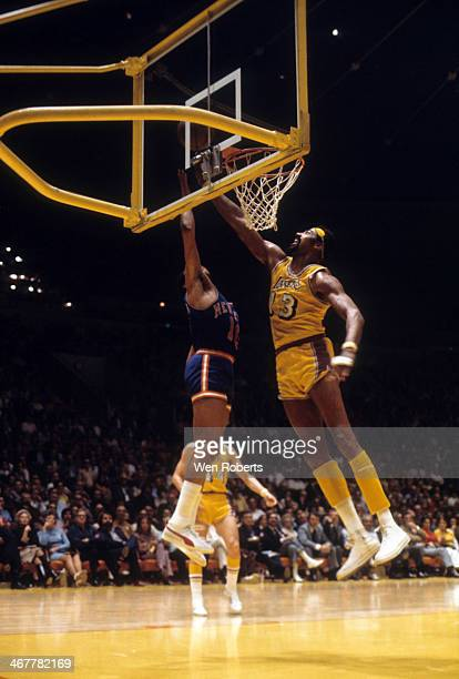 Wilt Chamberlain of the Los Angeles Lakers looks to block the shot attempt of Walt Frazier of the New York Knicks during the 1971-1972 season at the...
