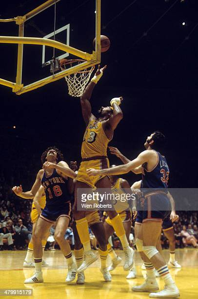Wilt Chamberlain of the Los Angeles Lakers puts up a shot as Phil Jackson and Jerry Lucas of the New York Knicks look for a rebound circa 1972 at the...