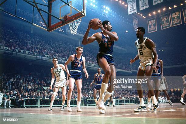 Wilt Chamberlain of the Philadelphia 76ers rebounds against Bill Russell of the Boston Celtics during a game played in 1967 at the Boston Garden in...