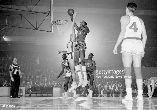 Wilt Chamberlain Philadelphia's sensational rookie lays one up and in despite defensive efforts of Knicks' Charlie Tyra in first period at Garden...