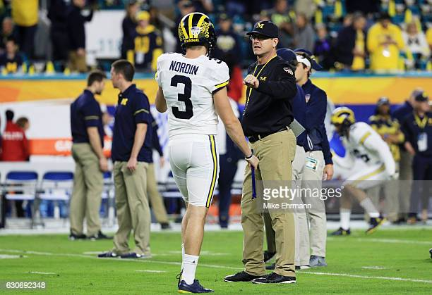 Wilton Speight talks to head coach Jim Harbaugh of the Michigan Wolverines prior to their Capitol One Orange Bowl game against the Florida State...