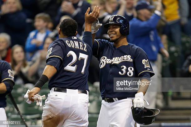 Wily Peralta of the Milwaukee Brewers and Carlos Gomez celebrates after reaching on a single hit by Jonathan Lucroy in the bottom of the fifth inning...